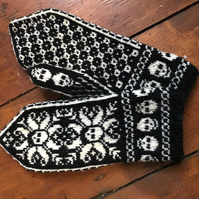 A pair of black and white mittens with a pattern of skulls on the back of the hand