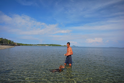 A dog and his master swimming during low tide at the beach of Inopacan, Leyte