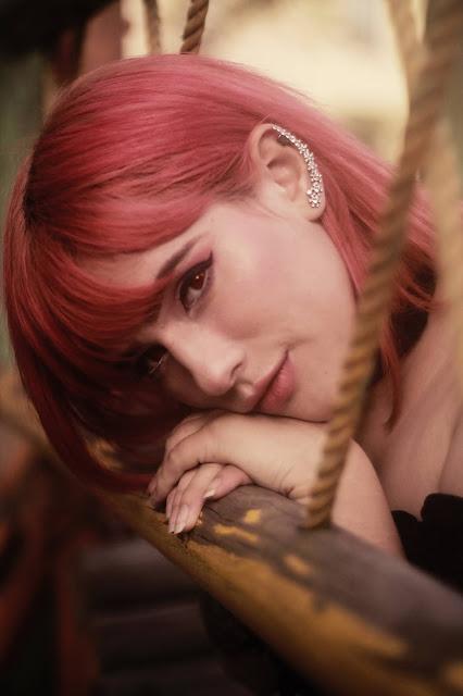Pink-haired girl wearing ear climbers-style earrings.