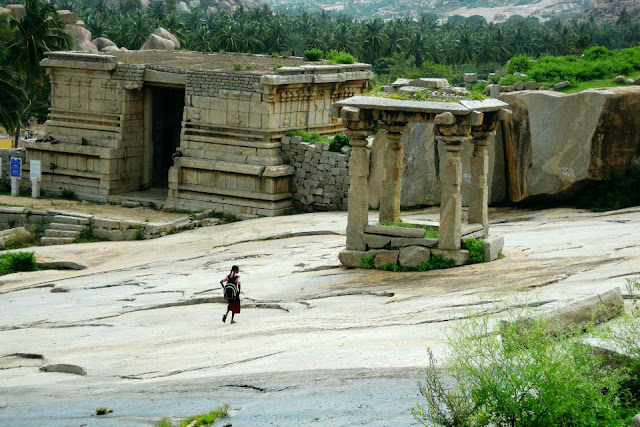 A lone schoolgirl makes her way across the ruins on Hemkuta Hill in Hampi