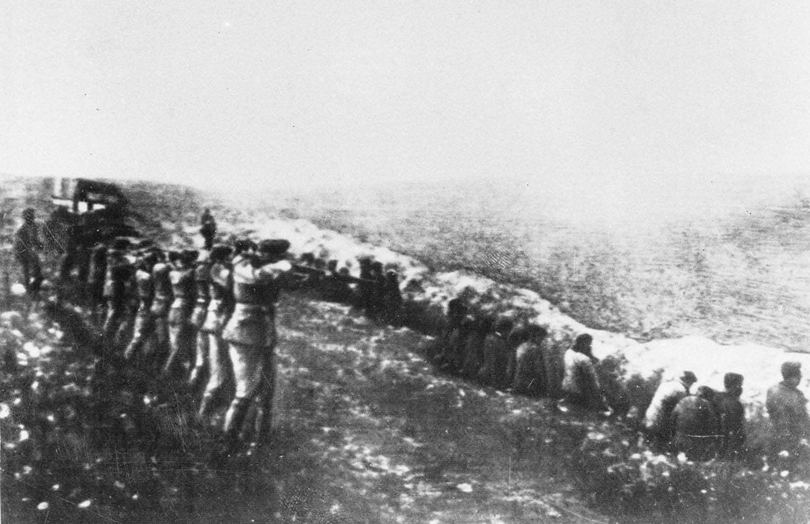 This photo was taken from a the body of a dead Germany officer killed in Russia, showing a German firing squad shooting Soviet civilians in the back as they sit beside their own mass grave in Babi Yar, an infamous ravine in the Ukrainian capital of Kiev, in 1942. Between 1941 and 1942, an estimated 100,000 to 150,000 Jews, Soviet prisoners, communists, gypsies, Ukrainian nationalists and civilians were executed by the Germans in Babi Yar.
