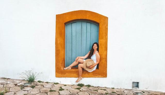 Menina sentada em uma janela azul com batente laranja