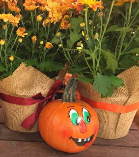 Decorated pumking infront of flower pots.