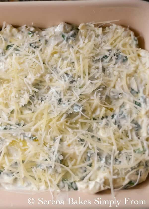 Spinach Artichoke Dip in pan covered with grated cheese ready to be baked.