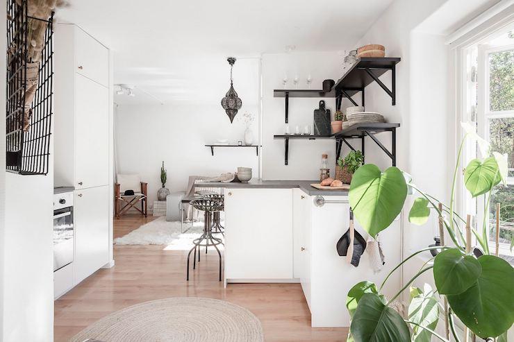 Cocina decorada en blanco y negro, abierta al salón.