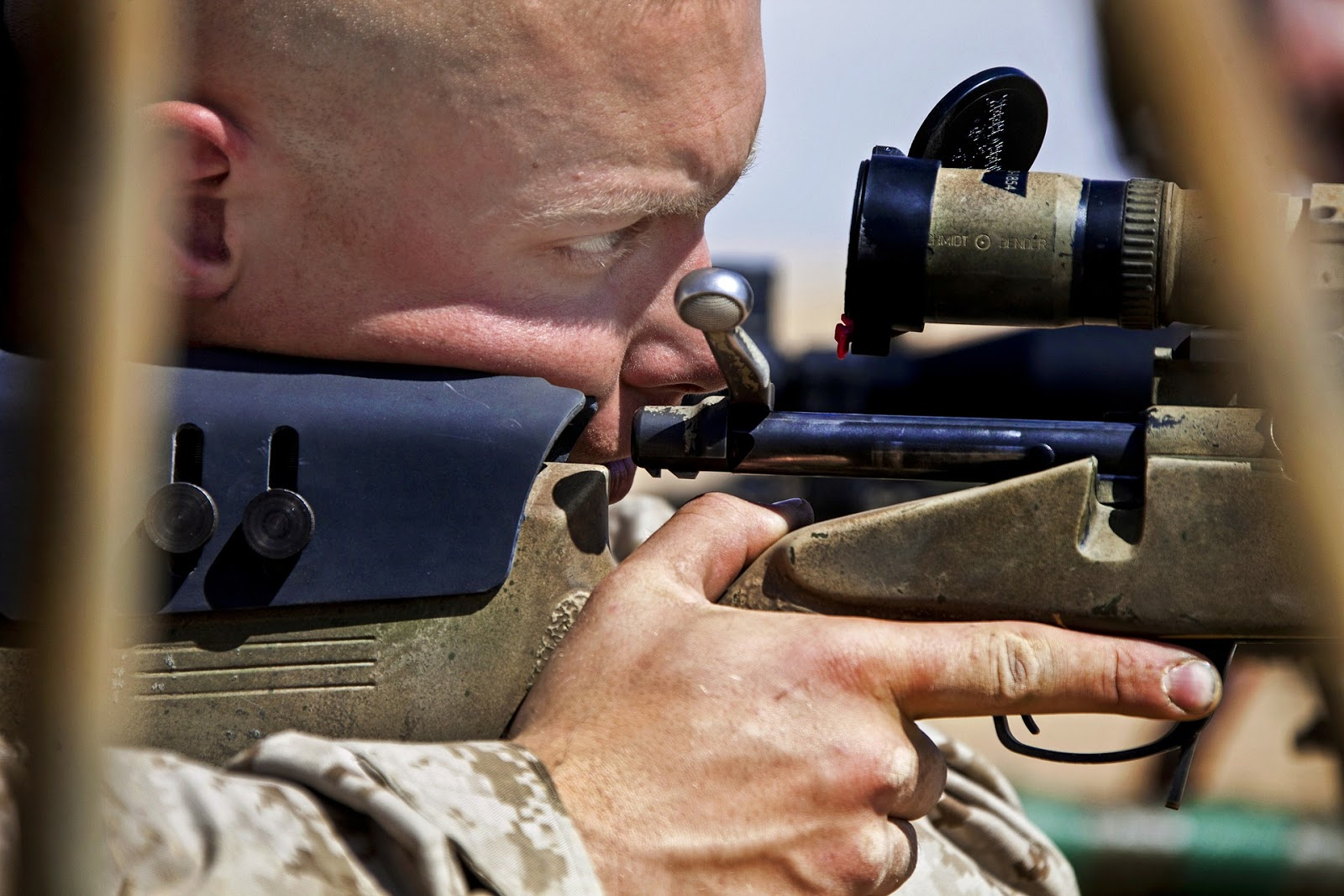 close up of army sniper looking down the scope of his rifle for blog post about war movie snipers
