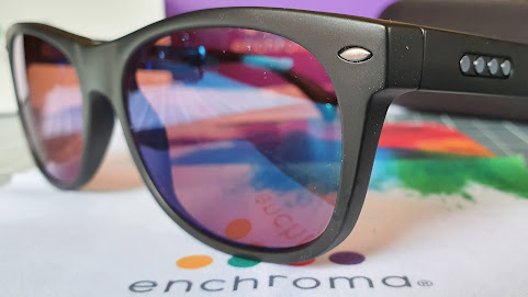 EnChroma Colby age 10+ sunglasses on a cloth with the Enchroma logo