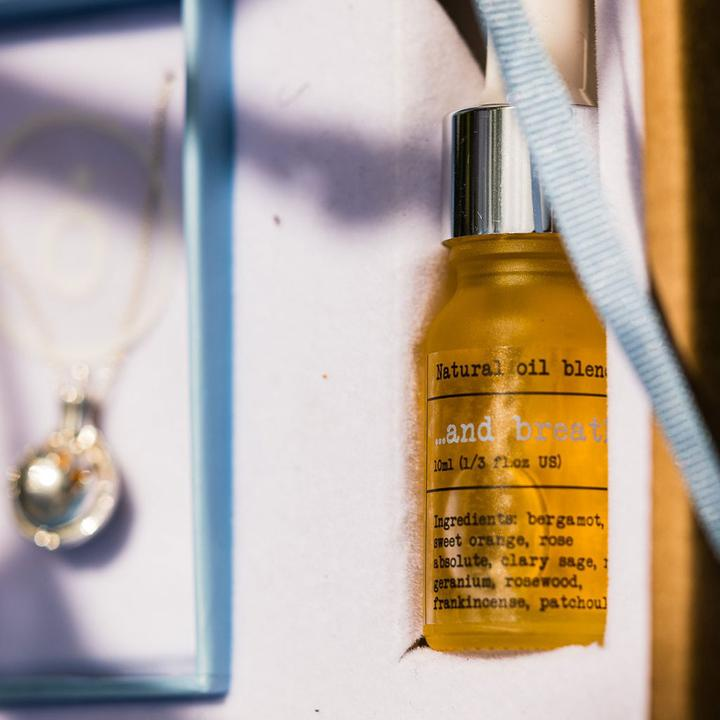 Perfino essential oil blend And Breathe with an ethical aromatherapy necklace hanging off to the side in the background