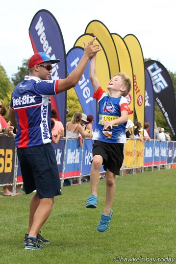 Right: Lincoln Paton, high-five congratulations - Sanitarium Weet-Bix Tryathlon at Frimley Park, Hastings. photograph
