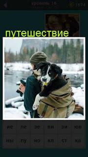 у мужчины с фотоаппаратом за спиной в рюкзаке находится собака