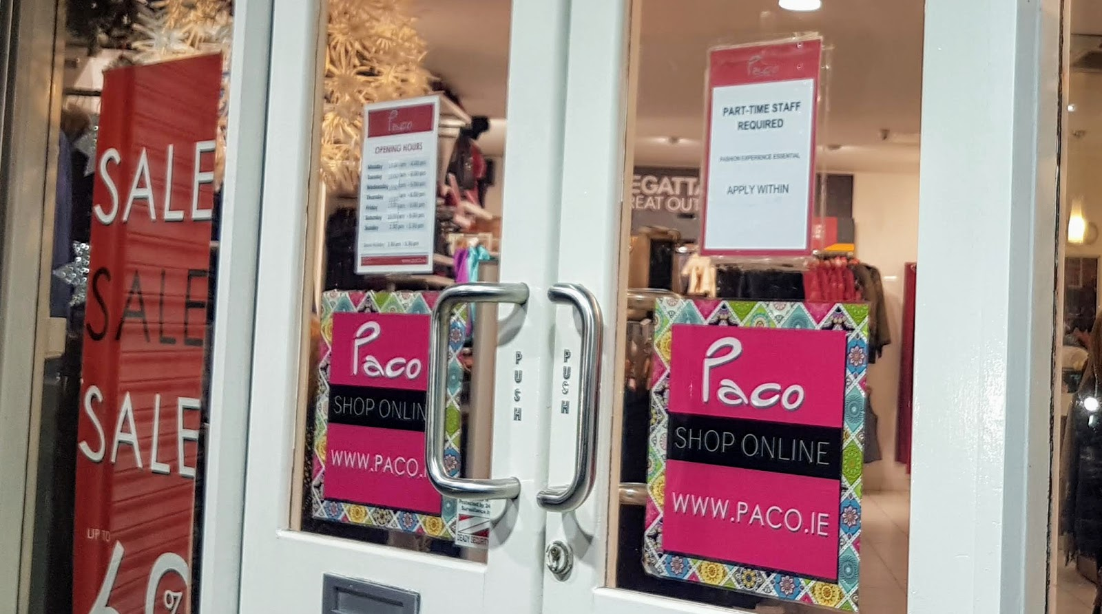 shop doors with opening hours sign at Paco Irish-fashion store in Galway city