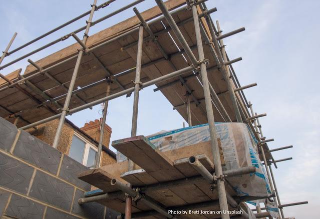 Construção de casa, com andaimes e sacos de cimento