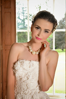 Girl with bouncy ponytail hairstyle similar to Audrey Hepburn with a fifties style bridal gown and big beaded necklace