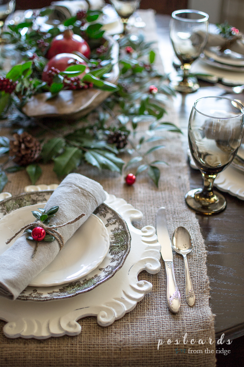 The vintage silverware and pretty wood charger plate add the perfect touch to this rustic Christmas table setting.