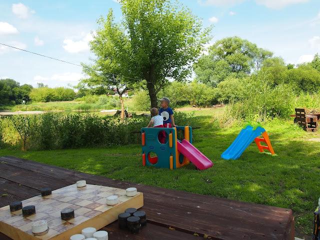Dzieci bawią się na mini placu zabaw. Na pierwszym planie eko planszówka- warcaby.
