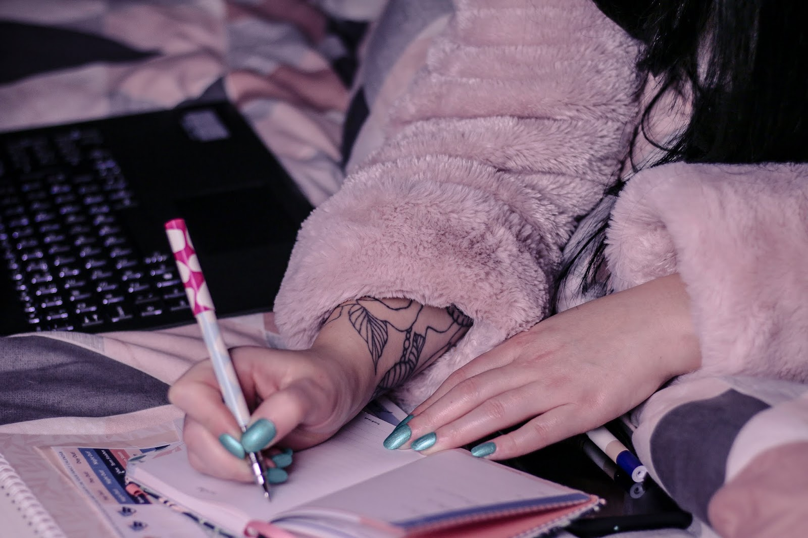 Close up photo of girl writing in diary, wearing a pink robe sitting on a bed with pink geometric bedding. There is a black laptop in the background out of focus