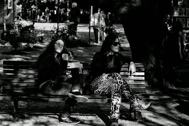 Dos  mujeres a la sombra en un banco del parque
