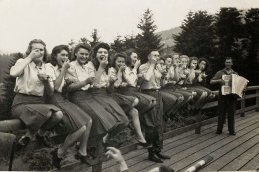 Doce auxiliares de las SS se sientan felices en una barandilla de la cerca, comiendo los arándanos que les dio un oficial de las SS.