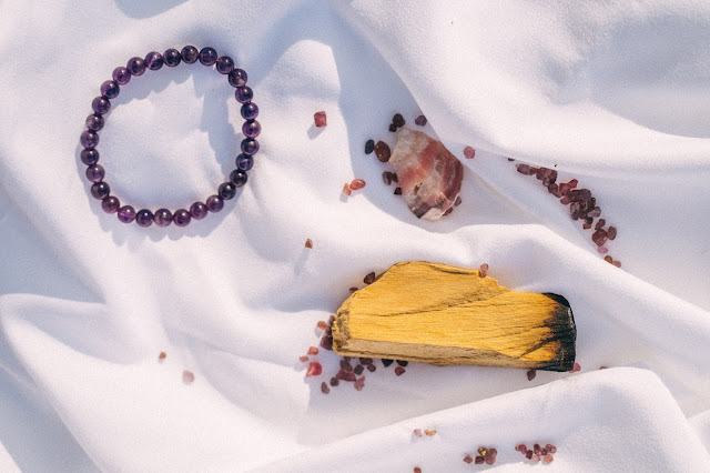 A purple beaded necklace and several pieces of crystals shot flatlay-style on a white piece of cloth.