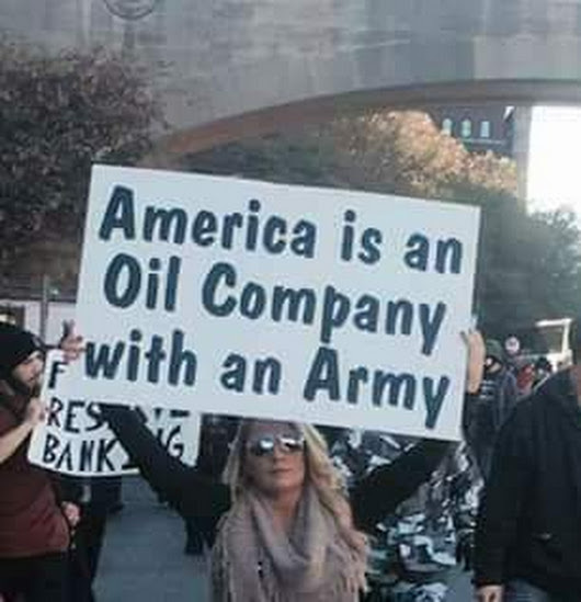 Lady holding sign stating: America is an Oil Company with an Army