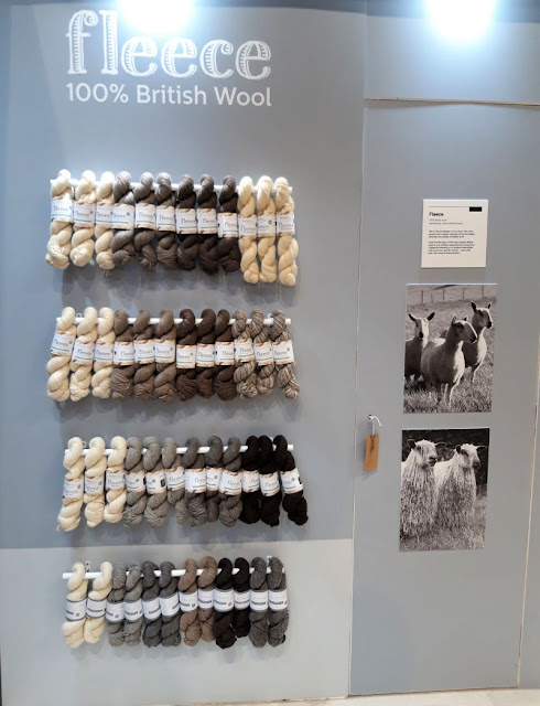 Image shows rows of skeins of natural coloured yarn.  On the right are pictures of sheep