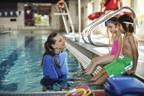 une maitre nageuse et des enfants au bord de la piscine