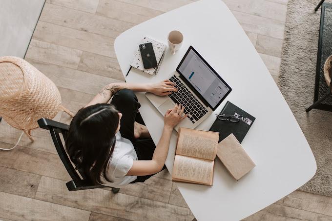 Mulher sentada usando laptop em uma mesa branca. Livros, caderno, caneta, óculos, celular e caneca também estão sobre a mesa.