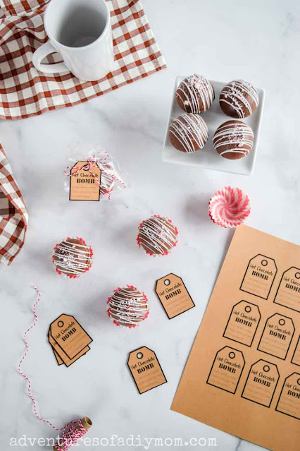 an overhead view of several hot chocolate bombs, printable tags, a mug, and a packaged hot chocolate bomb ready to gift