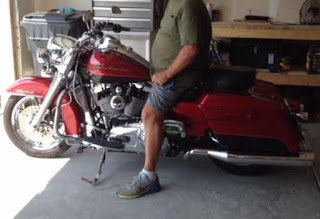 Motorcycle in garage with man on it.