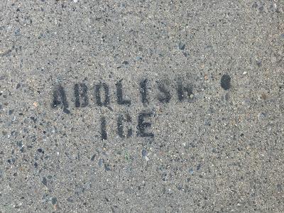 """""""Abolish ICE"""" spraypainted on sidewalk."""
