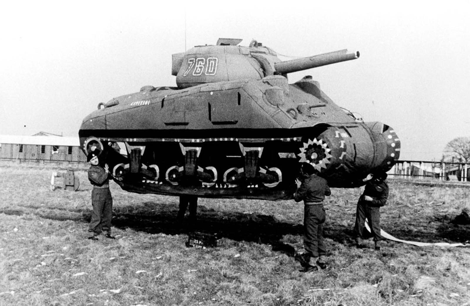 Soldiers lift up an inflatable rubber dummy tank in England. 1939.