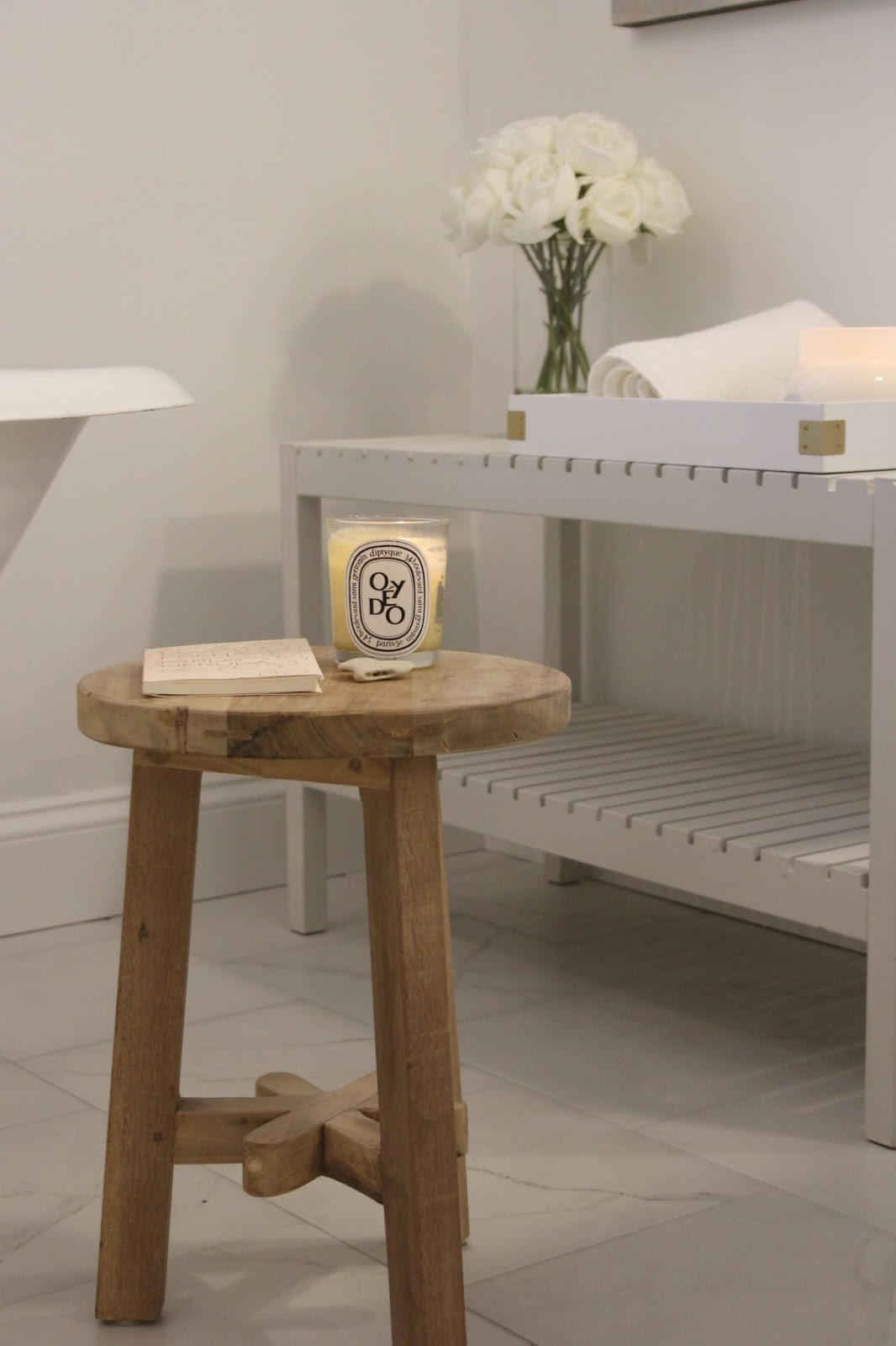 A 3-legged stool in my bathroom near the clawfoot tub has a Diptyque candle and a book of poetry. White roses in the background. #bathroomdecor #hellolovelystudio #rusticstool #diptyque