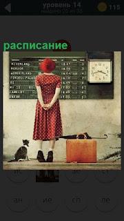 Около расписания на доске стоит одинокая девушка с чемоданом и кошкой рядом