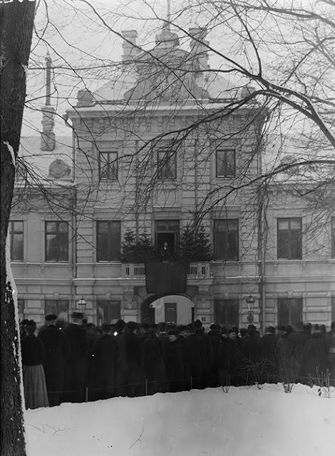Ihmisjoukko seisoo vanhan talon edustalla. Maassa on lunta ja mies puhuu parvekkeella.