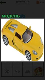 На поверхности стола стоит модель желтого цвета автомобиль
