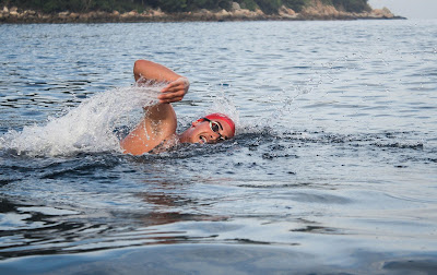 Image of a man swimming in open water. How to conquer open water swimming
