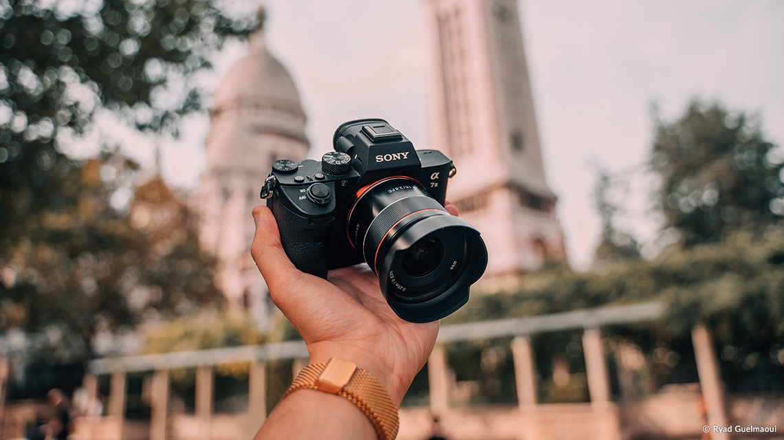 Объектив Samyang AF 18mm f/2.8 FE с камерой Sony в руке