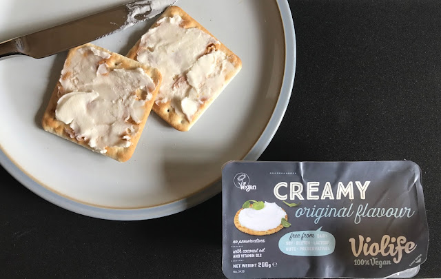 A plate with 2 crackers with cream cheese on and a packet of Creamy Violife