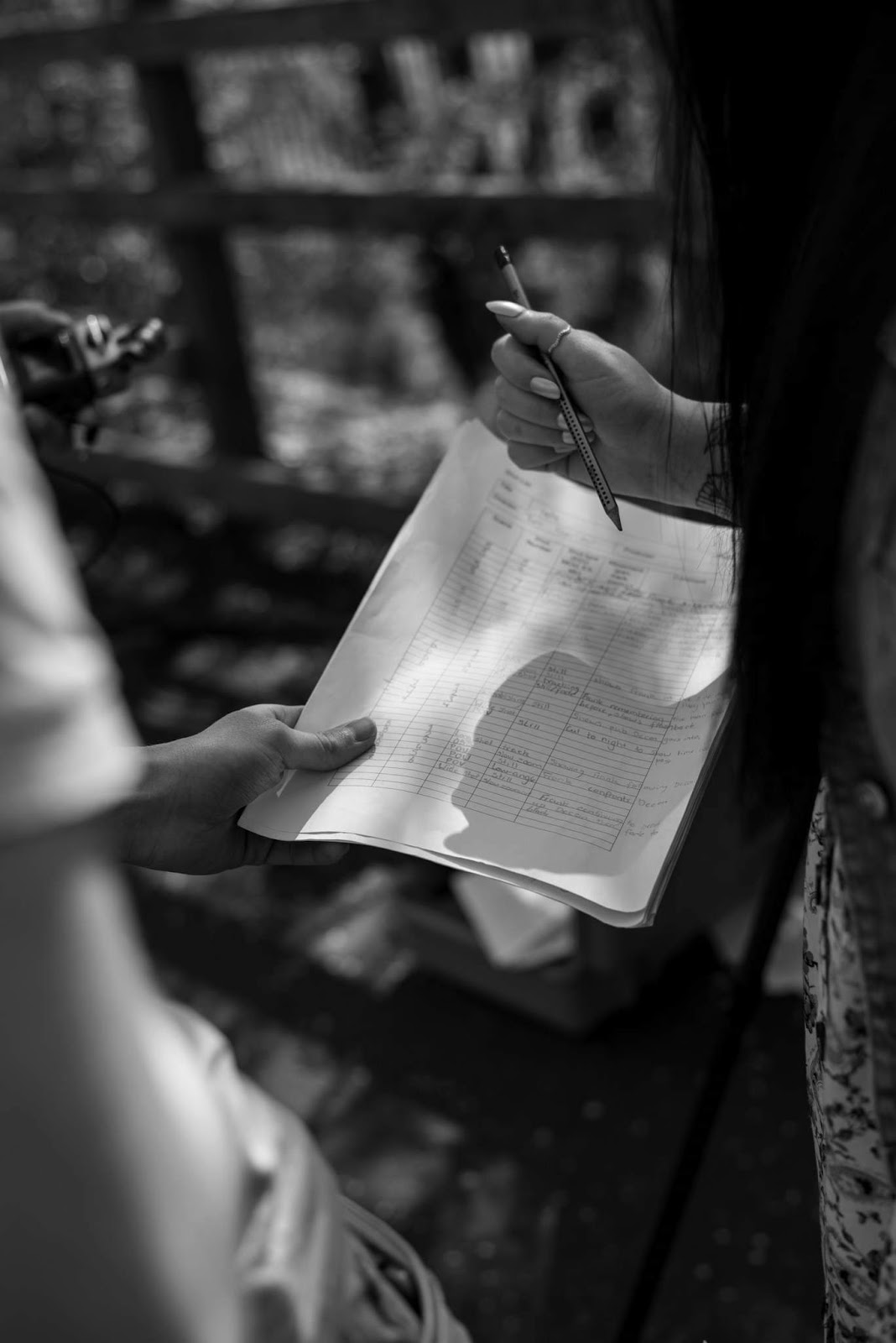 A black and white photo by Andrew dunn, a close up of a shot list with a man holding the paper and myself looking at the paper