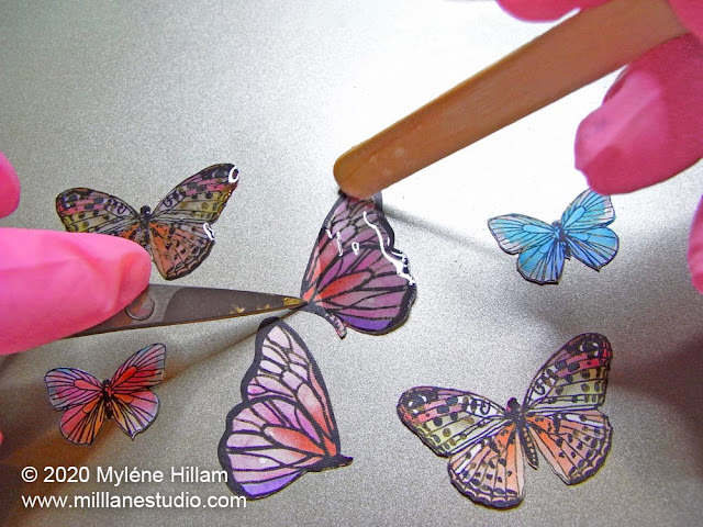 Painting resin onto the butterfly cutouts with a wooden stir stick