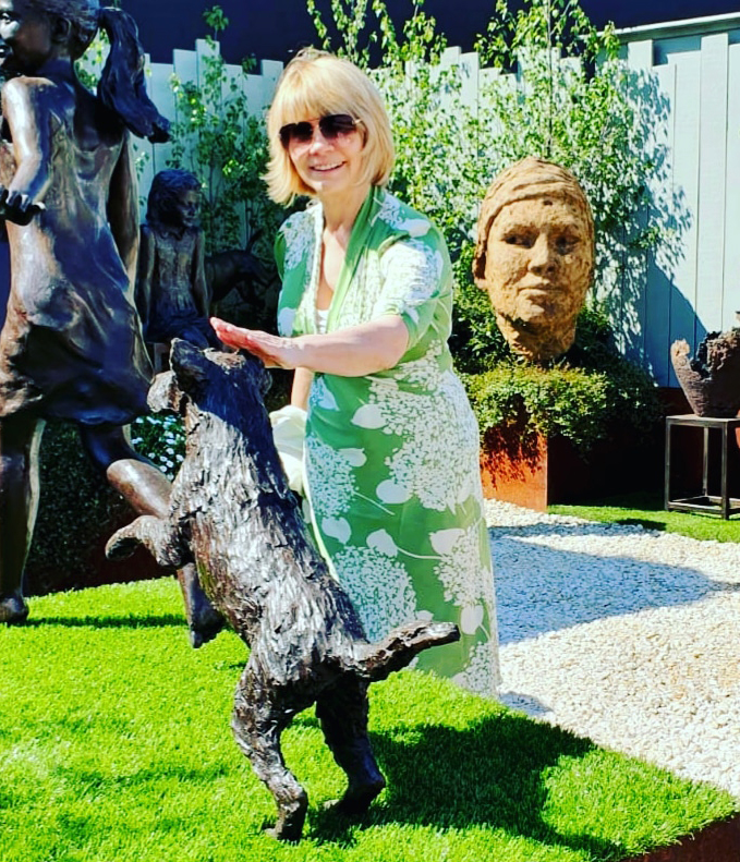 Style blogger Gail Hanlon patting a dog sculpture at the Chelsea Flower Show