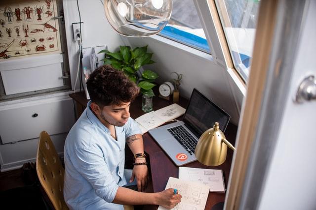 Homem sentado enquanto escreve na frente do Macbook