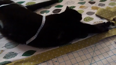 Black cat stretches full length on multicolored leaf against white fabric, a tape measure wrapped around her body