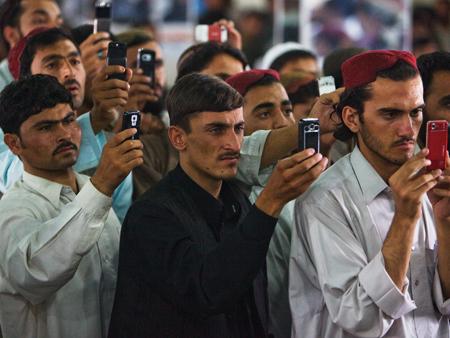 iludidos em estar usufruindo as coisas boas da vida, trabalhadores afegãos ostentam seus modernos celulares