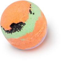 A golden spherical bath bomb with a crack on the side of it filled with orange and red powder on a bright background
