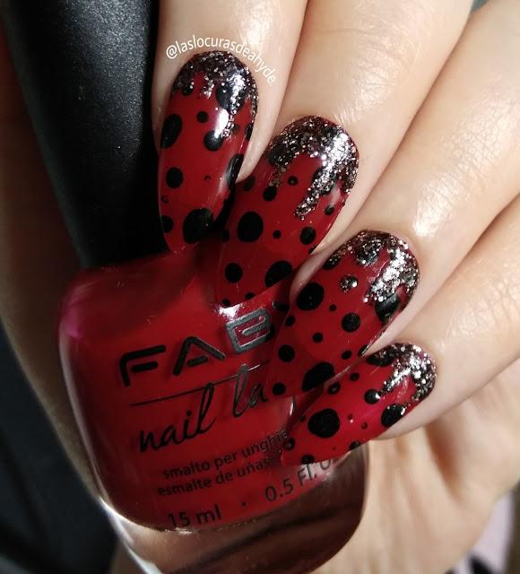 nail art de mariquita, base roja con puntitos en negro. zona de la cuticula con brillos negros