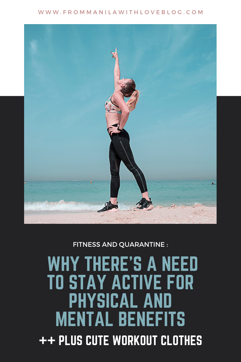 woman in workout clothes pointing to the sky at the beach