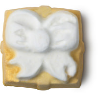 A close up of a square bright yellow sparkly bath bomb with a white engraved bow on top on a bright background