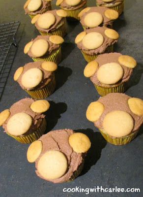 cupcakes with chocolate frosting and nilla wafers ready to be made into monkey faces
