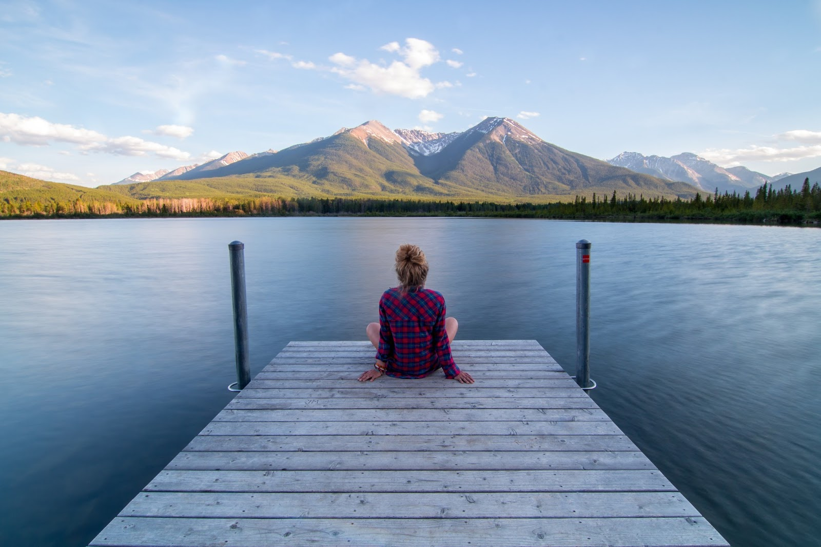 Woman on a jetty looking over a lake and mountains. 52 is a great time to think about how to find meaning and purpose in later life.